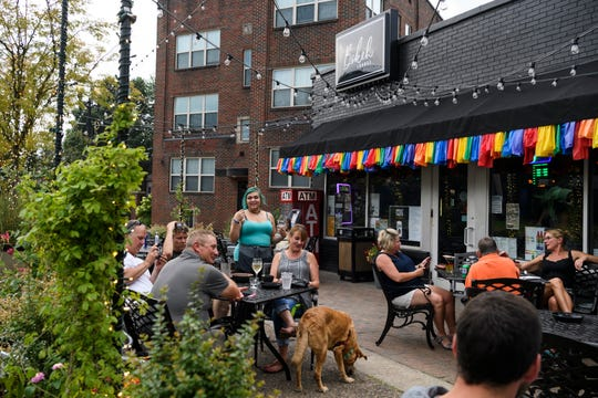 People relax on the front patio of Bokeh Lounge as they listen to Nick Hamilton, not pictured, play music in the Haynie's Corner Arts District neighborhood, Wednesday, June 26, 2019. Hamilton performs for patrons every Wednesday night.