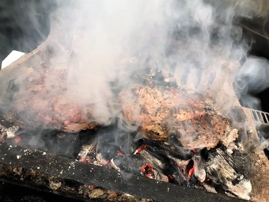 Steaks cooking directly on coals at Amy's on Franklin.