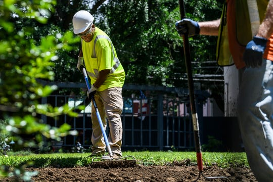 Workers spread new soil after digging up contaminated soil outside of a house on the 400 block of Southeast First Street, which is located in the Jacobsville Neighborhood Soil Contamination Superfund Site's OU2 South focus area, in Evansville, Thursday, June 27, 2019. Around 400 properties are expected to be cleaned up during the 2019 construction season.