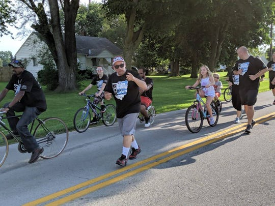 Jay Cullen runs with a group of officers, community members and Sandusky County Developmental Disabilities during the annual Law Enforcement Torch Run.