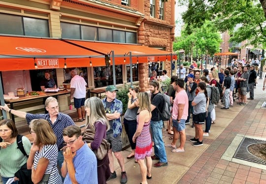 Crowds were out the door and well into Old Town Square waiting for the opening of Next Door American Eatery at the corner of College and Mountain avenues in Fort Collins.