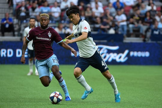 Colorado Rapids midfielder Kellyn Acosta, left, battles Vancouver's Inbeom Hwang for control of the ball during a June 22, 2019, match in Vancouver, British Columbia. The Rapids will play a home game at 8 p.m. Friday at Dick's Sporting Goods Park in Commerce City against the Los Angeles Football Club.