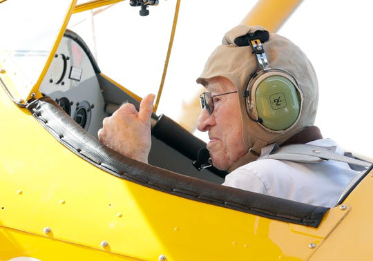 World War II Navy veteran Dutch Clark gives a thumbs up before taking off in an open cockpit, 1943 Stearman biplane with Darryl Fisher, pilot and founder of Ageless Aviation Dreams Foundation, on June 27, 2019, at Green Bay Austin Straubel International Airport in Ashwaubenon.