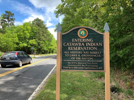 In a Friday, April 26, 2019 photo, a sign welcomes people to the Catawba Indian Nation's reservation near Rock Hill, S.C.  Two of the Carolinas' most prominent American Indian tribes are battling over geography and lucrative gambling turf. The Cherokee in North Carolina, with two casinos established in the mountains, say their opponents should stay in their own state to the south. The Catawba of South Carolina argue such state boundaries are artificial and shouldn't affect their effort to gain a foothold in the industry. (AP Photo /Jeffrey Collins)