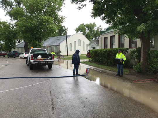 Cascade County workers pump water from the street near the Family Living Center at Montana ExpoPark on Thursday at about 5 p.m. following heavy rains.