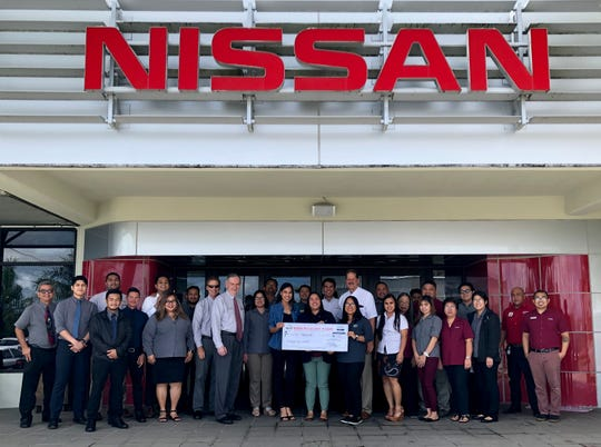 Nissan Guam officials present a check to the Girl Scouts. Through the annual Flag Run, the company raised $18,000 for Mañelu, Catholic Social Services and Guam Girl Scouts.