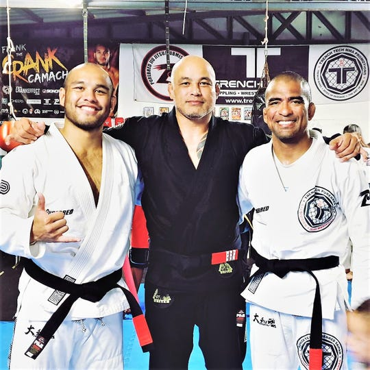 "Frank ""The Crank"" Camacho, left and Cuki Alvarez, right, received their black belts June 25 in Saipan. Purebred BJJ Guam owner and head instructor Stephen Roberto, center, conferred the promotions."