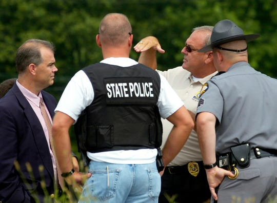 Henderson Police Chief Ed Brady talks with Kentucky State Police officers after a shot was fired through his police cruiser during a chase as Henderson and Evansville police officers tried to apprehend two suspected bank robbers at the U.S. 41-U.S. 60 cloverleaf. (Gleaner photo by Mike Lawrence) 07/01/2005