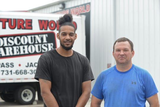 Furniture World Discount Warehouse employees Justin McKnight and Robert Miller stand in front of the Jackson, Tennessee, warehouse on June 27, 2019. Both men helped apprehend a shooting suspect in front of the store on June 23.