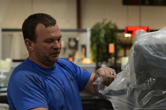Furniture World Discount Warehouse Manager Robert Miller removes plastic from a new couch on showroom floor in Jackson, Tennessee, on June 27, 2019. Miller helped apprehend a shooting suspect in front of the store on June 23.