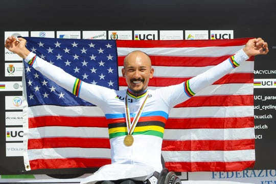 Para-cyclist Will Groulx brandishes the American flag in celebration at the 2018 UCI Para-cycling Road World Championships in Maniago, Italy.