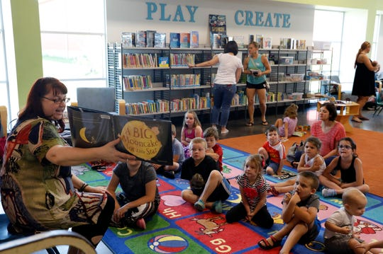 "Amber Glenaman, a library assistant, reads ""A Big Mooncake for Little Star"" to a group of children Wednesday morning, June 26, 2019, at the Fairfield County District Library Northwest branch in Greenfield Township. The branch offers a children's story time three days a week."