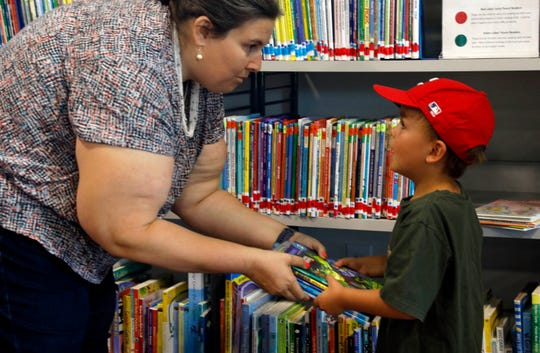 Tara Hutson, left hands Sawyer Herman, 6, a stack of books Wednesday morning, June 26, 2019, at Fairfield County District Library Northwest Branch in Greenfield Township. Sawyer, who will be in first grade at Pleasantville Elementary in the fall, is taking part in the library's summer reading program for the first time.