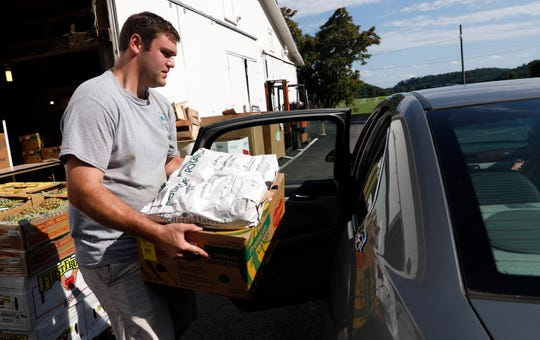Alex Smith, pantries coordinator for the Lancaster-Fairfield County Community Action Agency, carries a box of produce and baked goods to a waiting car Wednesday evening, June 27, 2019, in Lancaster.