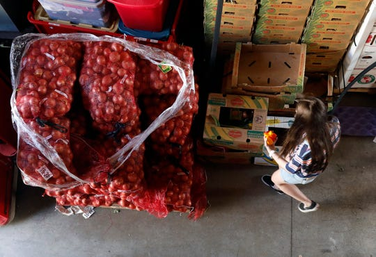 Isabelle Carter carries a handful of peppers to put in a box of produce Wednesday evening, June 26, 2019, at the Lancaster-Fairfield Community Action Agency in Lancaster. Volunteers spent the day prepare boxes of produce to be given to eligible families as part of the agency's monthly farmers market.