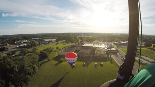Over the shoulder of Sullair balloon pilot Shawn Raya, a view of the launch field Wednesday, June 26, 2019 on the grounds of Howell Public Schools shows the Re/Max balloon taking off just behind Raya's balloon.