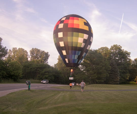 Shawn Raya, pilot of the Sullair balloon, lands in the front lawn of Melanie Hoffman Wednesday, June 26, 2019 on Golf Club Road east of Latson in Genoa Township. Hoffman and her 13-year-old son Nicholas came out to bid clear landing to the pilot as crew members from the chase vehicle ran to assist with the landing.