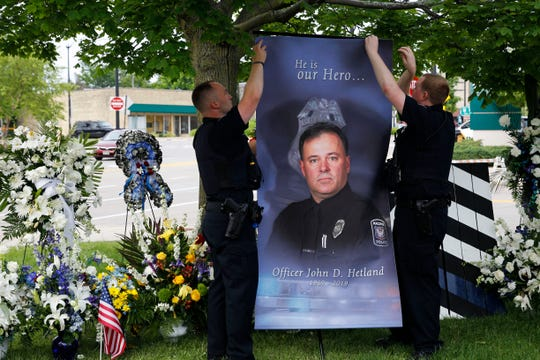 Racine police officers hang a photo of slain Police Officer John Hetland before a news conference Thursday to announce an arrest in his death.
