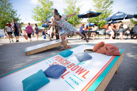 Festival goers enjoy a game of cornhole at the Summerfest Party Patio with Punch Bowl Social.
