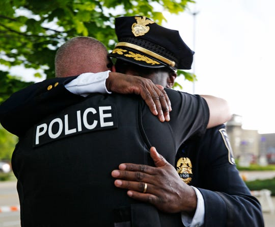 Racine Police Chief Art Howell, (facing camera) embraces another officer following a news conference Thursday to announce an arrest in the fatal shooting of Racine Police Officer John Hetland.