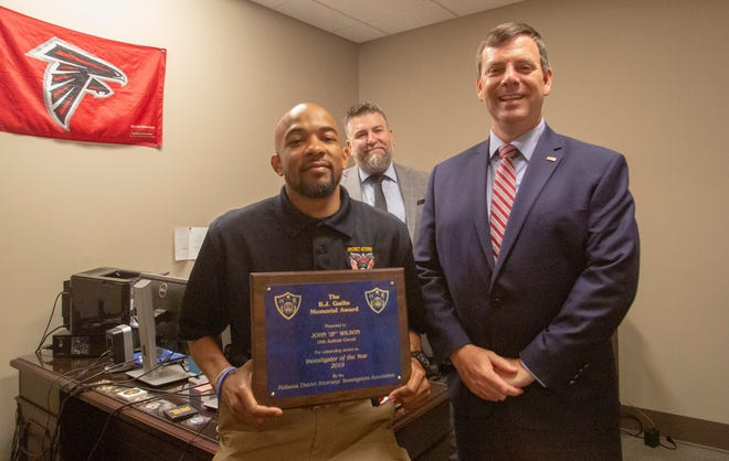 J.P. Wilson, the Alabama District Attorneys Association B.J. Gatlin Memorial Award Investigator of the Year winner, poses for a photograph with Montgomery County District Attorney Daryl Bailey and Deputy District Attorney Scott Green.