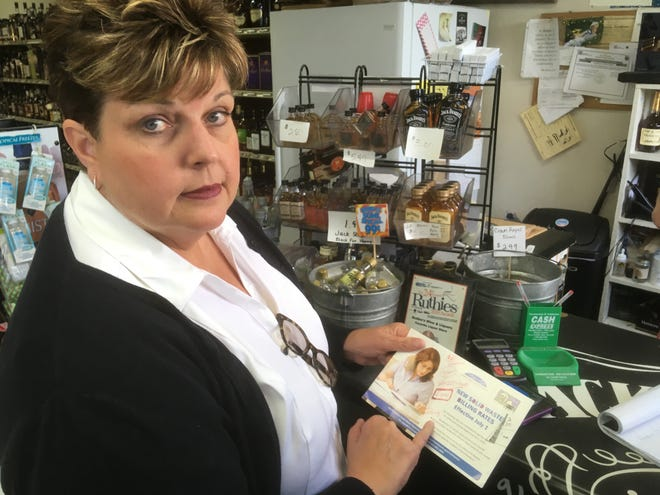 Barbara Hutson Fry, the owner of Bubba's Wine and Liquors in Murfreesboro, shows off a postcard from the city to explain monthly billing for trash at $30 per can, which would be $210 for her property. The city would not permit Fry to reduce the number of cans to save money on her bill, so she chose to opt out of the service and use a private hauler for $90 per month less.