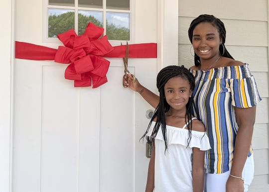 Kim Wilson and her daughter Destine cut the ribbon to their new home in Fairview on June 15, 2019.