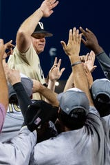 Vanderbilt coach Tim Corbin celebrates with his players after defeating Michigan in the College World Series finale Wednesday.