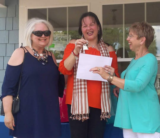 Women Build volunteers Cathy Culp (left) and Carol McDaniel (right) present the mortgage agreement and keys to future homeowner Maria Herrera at a dedication ceremony on June 15, 2019.