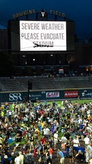 Fans evacuate Hawkins Field after lightning appeared in the area Wednesday.