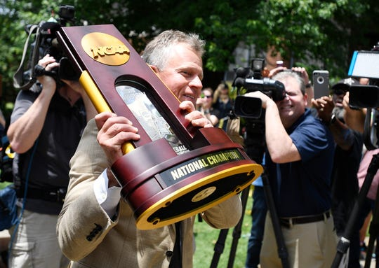 Vanderbilt head coach Tim Corbin holds the championship trophy as he greets fans after the team arrived at Hawkins Field in Nashville, Tenn., Thursday, June 27, 2019.
