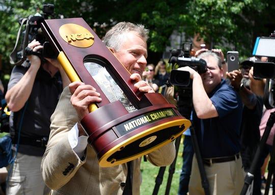 Vanderbilt head coach Tim Corbin holds the championship trophy as he greets fans after the team arrived at Hawkins Field in Nashville, Tenn., Thursday, June 27, 2019.
