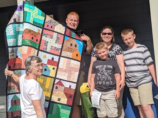 Members of St. Matthew Quilt Ministry presented the Alejandros with a hand-made quilt for their new home at the Habitat for Humanity dedication ceremony on June 15, 2019.