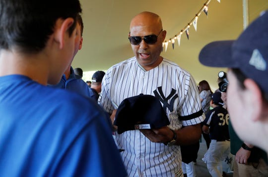 Yankees' Mariano Rivera signs baseball cap for young fans during a private Baseball Clinic in London, Thursday, June 27, 2019. The Yankees are hosting for approximately 100 youth in the London community in conjunction with the London Meteorites Baseball and Softball Club this private Baseball Clinic. (AP Photo/Frank Augstein)