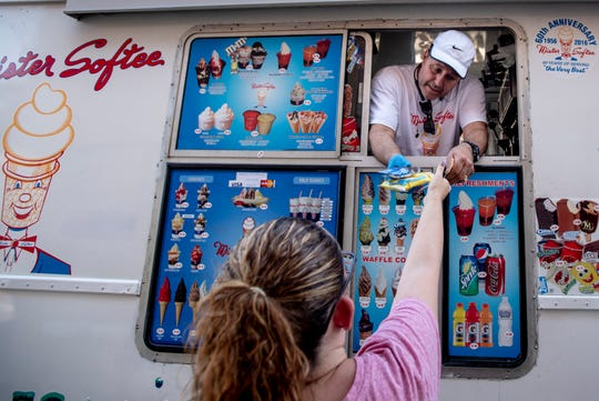 Sergio Gonzalez hands a customer and frozen treat from his Mister Softee ice cream truck during a stop in Moonachie on Wednesday June 26, 2019.