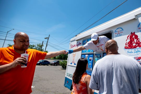 Mister Softee franchise owner Sergio Gonzalez hands a napkin to Eric Skinner after ordering a mango shake in Secaucus on Wednesday June 26, 2019.