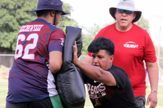 Justin Morales punches the bag during a line backer drills as coach Richard Perales looks on.