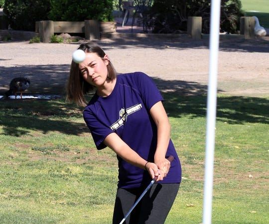 Shelby Turner, 22, eyes her chip shot on No. 18 at Rio Mimbres golf course. Turner capped her golf career at Western New Mexico University with five school records.