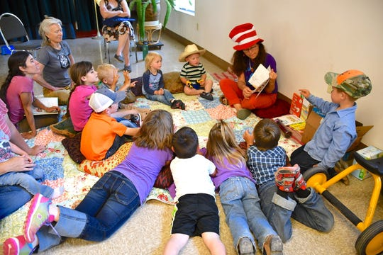 Librarian Lynn Neidermayer reads to the pre-school children attending the Summer Reading Program.