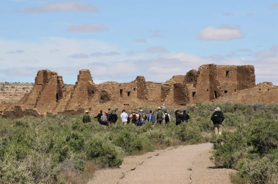Visitors follow a path to Pueblo Bonito at Chaco Culture National Historic Park on May 28. The park is part of the federal government's holdings in San Juan County.