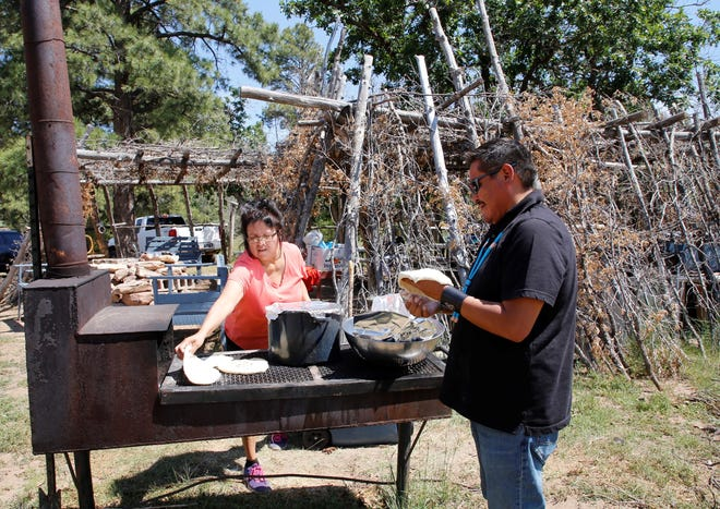 From left, Harriet Chee, a member of the Tooh Haltsooí Chapter Wellness and Healthy Foods Team, and Kevin Begay, chapter manager, prepare lunch on June 25 on Ch'ooshgai Mountain in Sheep Springs.