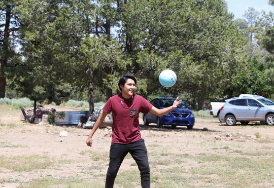 Geno Chicharello serves the ball during a volleyball game as part of recreation day on June 25 on Ch'ooshgai Mountain in Sheep Springs.