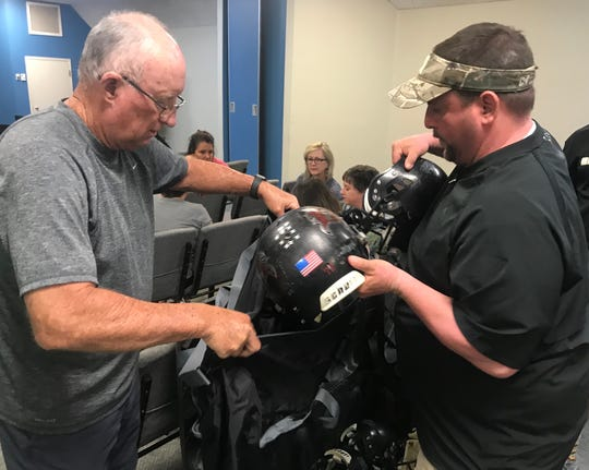 Pace Athletic Director Robert Freeman and Milton football head coach Harry Lees load up helmets at Olive Baptist Church for their football-oriented mission trip to Brazil that begins this Sunday.