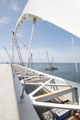 Workers on Thursday install the 800,000-pound steel arch atop the eastbound expanse of the new Pensacola Bay Bridge.