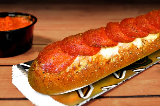Pepperoni Pretzel Melts are made with Italian spices, melted cheese blend, and pepperoni slices nestled on top of a fresh baked soft pretzel rod accompanied with a cup of Philly Pretzel Factory's zesty marinara sauce.