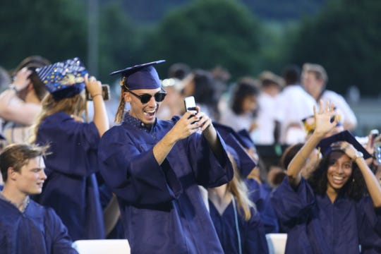 Students react during a sudden storm at the Highland High School class of 2019 graduation ceremony Wednesday night.