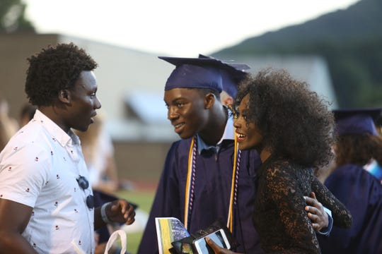 Kingsley Ogelle, center, celebrates at the Highland High School class of 2019 graduation ceremony Wednesday night.
