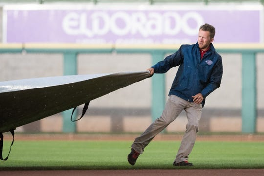 Joe Hill, the director of operations for Greater Nevada Field, for both the Aces baseball team and 1868 FC soccer team, pulls a tarp over the field earlier this season.