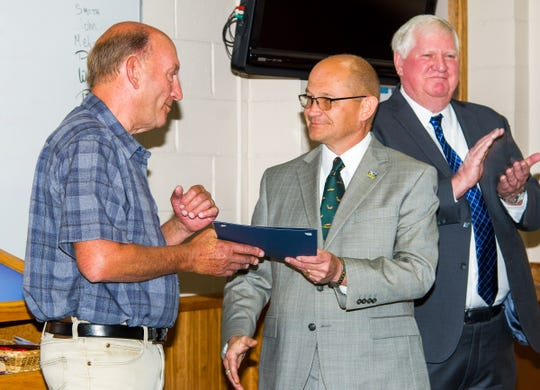 """Yerington Mayor George Dini (left) accepts a resolution declaring June 24 """"George Dini Day"""" from County Manager Jeff Page. At right is mayor-elect John Garry, who replaced Dini as mayor on July 1."""