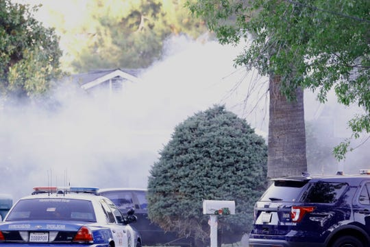 Tear gas drifts from a house on Miller Street in Redding after a SWAT team fired canisters of the chemical agent during a standoff Wednesday, June 26, 2019.